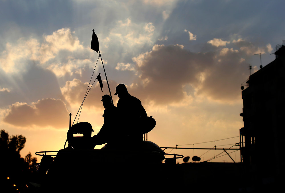 Description of . Egyptian army soldiers sit on top of their tank as the sun sets outside the presidential palace, background, in Cairo, Egypt, Saturday, Dec. 8, 2012. Egypt\'s military warned Saturday of \'disastrous consequences\' if the crisis that sent tens of thousands of protesters back into the streets is not resolved, signaling the army\'s return to an increasingly polarized and violent political scene.(AP Photo/Hassan Ammar)