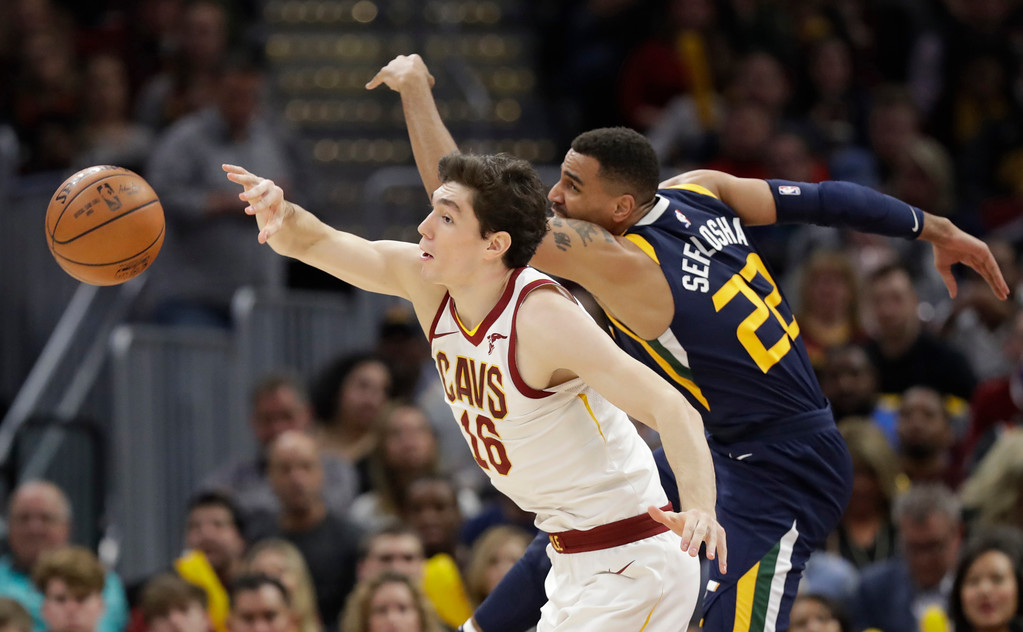 . Cleveland Cavaliers\' Cedi Osman (16), from Turkey, and Utah Jazz\'s Thabo Sefolosha (22), from Switzerland, battle for a loose ball in the second half of an NBA basketball game, Saturday, Dec. 16, 2017, in Cleveland. (AP Photo/Tony Dejak)