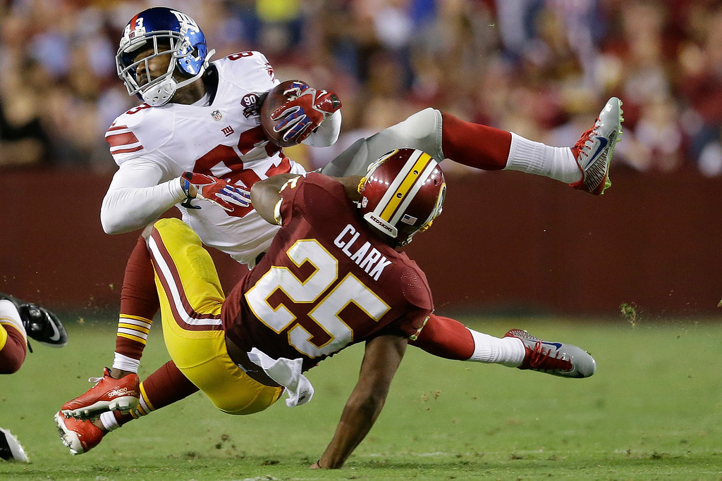 . New York Giants wide receiver Preston Parker (83) is stopped by Washington Redskins free safety Ryan Clark (25) during the first half of an NFL football game in Landover, Md., Thursday, Sept. 25, 2014. (AP Photo/Patrick Semansky)