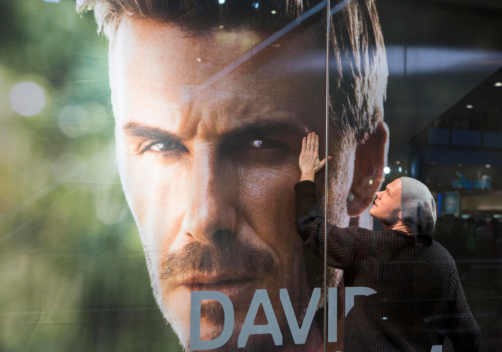 . A window dresser adjusts a giant poster showing a portrait of British soccer player David Beckham in the show window of a clothing chain shop at Potsdamer Platz shopping center in Berlin, Germany (AP Photo/Gero Breloer)