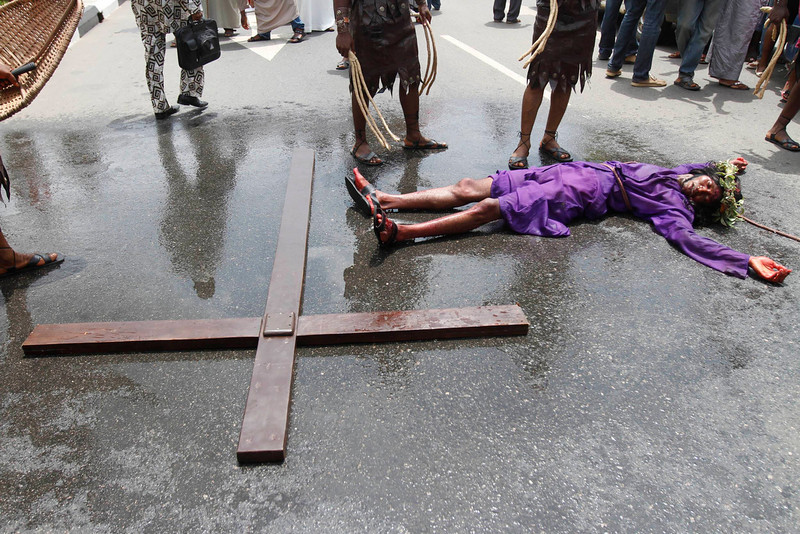 . A man playing the role of Jesus Christ lies on a road beside a cross during a ritual procession re-enacting the death of Jesus in Nigeria\'s commercial capital Lagos March 29, 2013. Holy Week is celebrated in many Christian traditions during the week before Easter. REUTERS/Akintunde Akinleye