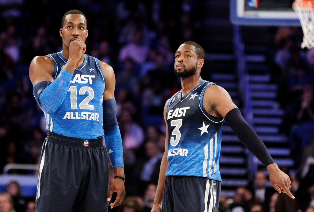 . Eastern Conference\'s Dwight Howard (12), of the Orlando Magic, and Dwyane Wade (3), of the Miami Heat, talk at midcourt during the second half of the NBA All-Star basketball game, Sunday, Feb. 26, 2012, in Orlando, Fla. The Western Conference won 152-149. (AP Photo/Chris O\'Meara)
