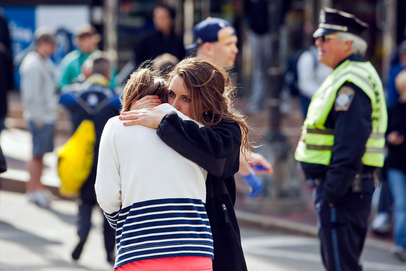 . A woman comforts another, who appears to have suffered an injury to her hand, after explosions interrupted the 117th Boston Marathon in Boston, Massachusetts April 15, 2013. Two people were killed and 23 others injured after two explosions struck the Boston Marathon as runners crossed the finish line on Monday, Boston police said.        REUTERS/Dominick Reuter