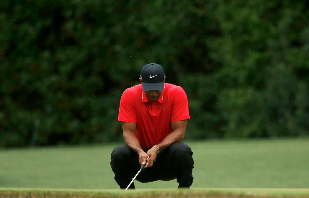 Description of . Tiger Woods of the U.S. reacts to missing a birdie putt on the fourth green during final round play in the 2013 Masters golf tournament at the Augusta National Golf Club in Augusta, Georgia, April 14, 2013.   REUTERS/Phil Noble