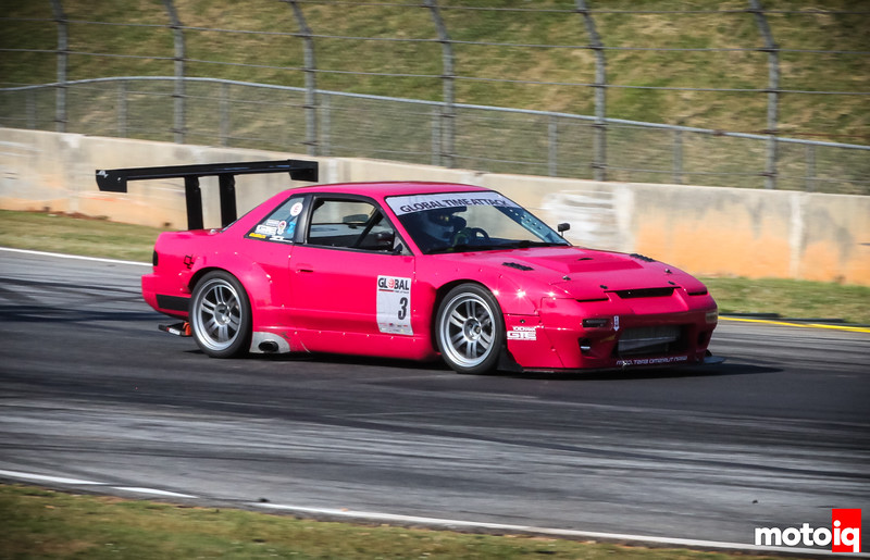 Pink-ish 240SX driving to right of frame braking for corner
