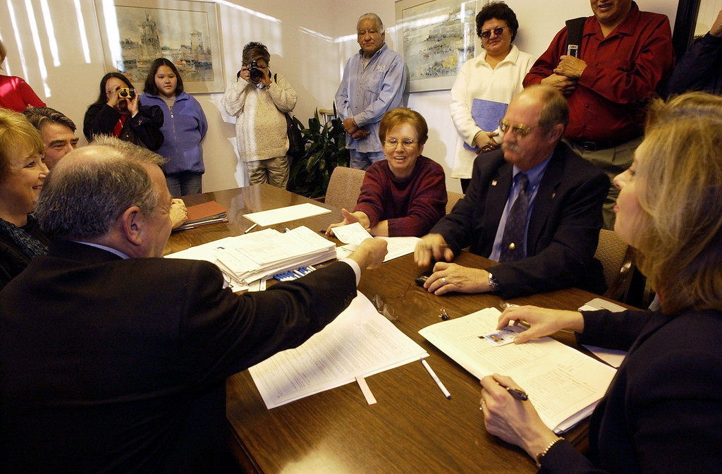 . Jim Druck, president of Southwest Casino and Hotel Corp, hands over a check to Tootie Dawson and husband William Dawson after his purchase of the land where the Sand Creek Massacre took place. The property sold for $1.5 million. December 2, 2002. (Photo by John Leyba/The Denver Post)