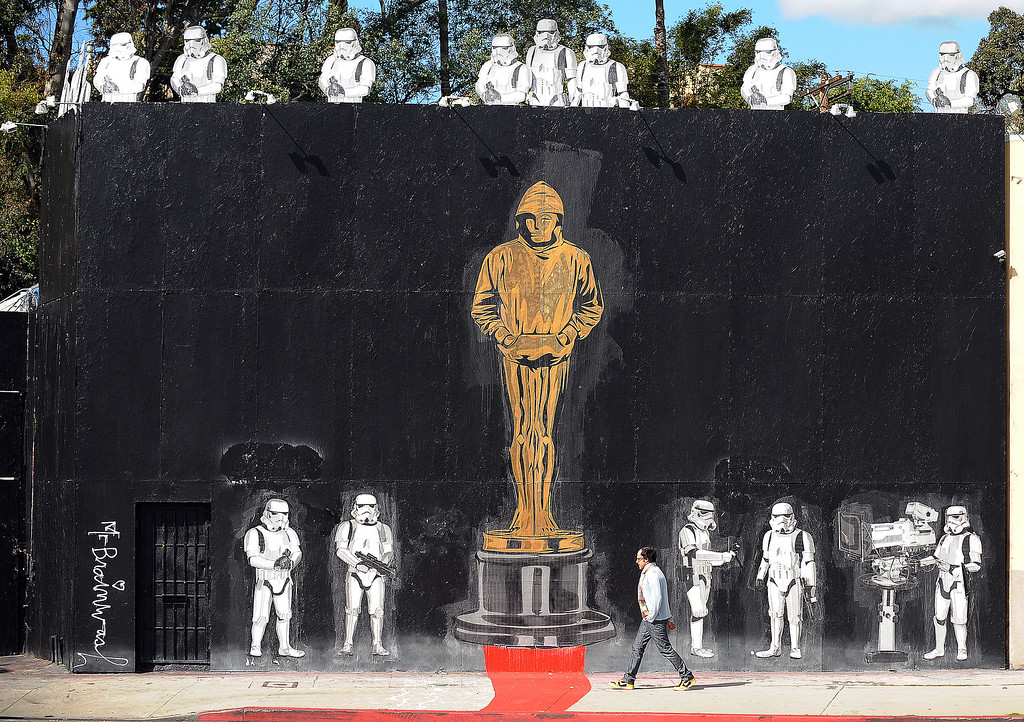 ". A man walks in front of a mural celebrating Banksy\'s Academy Award achievement signed by Mr. Brainwash in Los Angeles, California on February 17, 2011. Banksy is nominated for best documentary for ""Exit Through the Gift Shop\"" at the Oscars, due to be announced on February 27 at the climax of Tinseltown\'s annual awards season.  (GABRIEL BOUYS/AFP/Getty Images)"