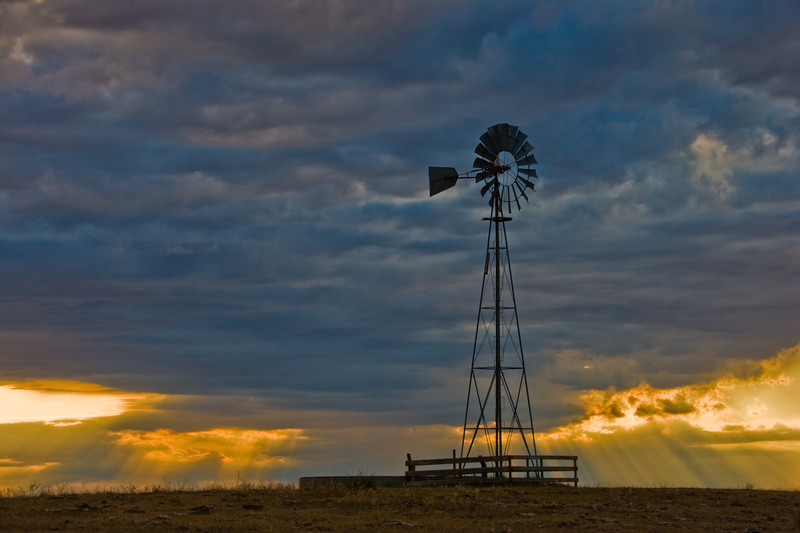 Golden god rays streak from clouds behind a water station windmill at Pawnee Buttes, in Pawnee National Grasslands, north of Greeley Colorado.