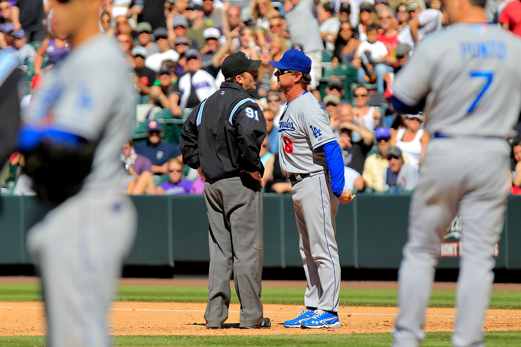 . Los Angeles Dodgers manager Don Mattingly (8) argues with umpire Brian knight about a play at second   during the sixth inning of the MLB National League baseball game against the Colorado Rockies Saturday June 1, 2013 in Denver.  Mattingly was ejected from the game for the first time this season. (AP Photo/Barry Gutierrez)