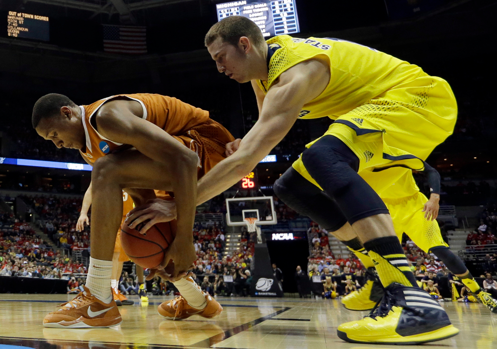 Description of . Texas' Demarcus Holland, left, and Michigan's Nik Stauskas battle for a loose ball during the first half of a third-round game of the NCAA college basketball tournament Saturday, March 22, 2014, in Milwaukee. (AP Photo/Morry Gash)