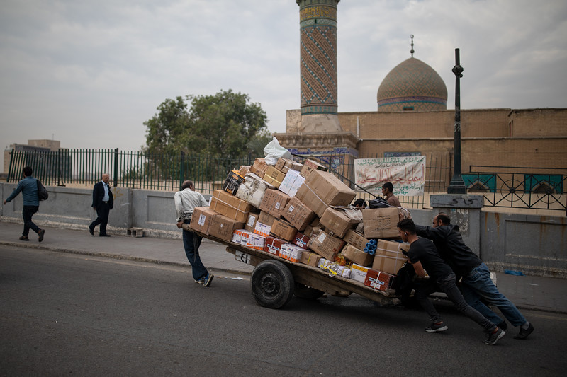 Men pushing a cart of boxes outside Mosque Wazzar, Central Baghdad.