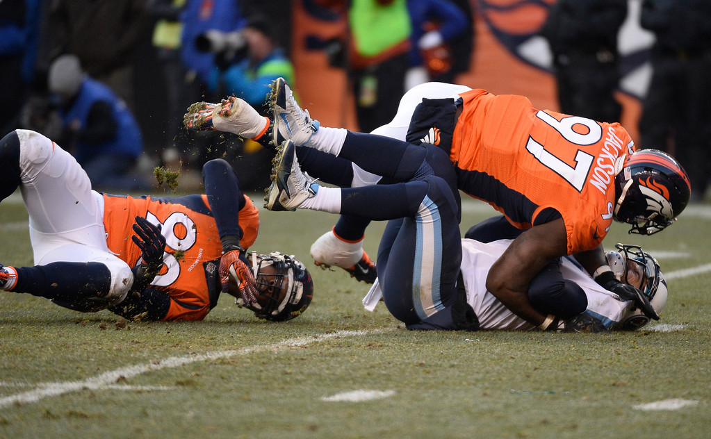 . Denver Broncos defensive end Malik Jackson (97) and defensive end Shaun Phillips (90) tackle Tennessee Titans quarterback Ryan Fitzpatrick (4) in the second quarter.  (Photo by John Leyba/The Denver Post)