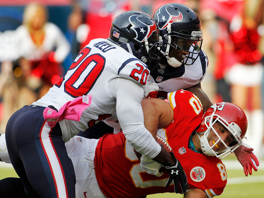 . Kansas City Chiefs tight end Anthony Fasano (80) is tackled by Houston Texans safety Ed Reed (20) and D.J. Swearinger (36) during the first half of an NFL football game at Arrowhead Stadium in Kansas City, Mo., Sunday, Oct. 20, 2013. (AP Photo/Colin E. Braley)