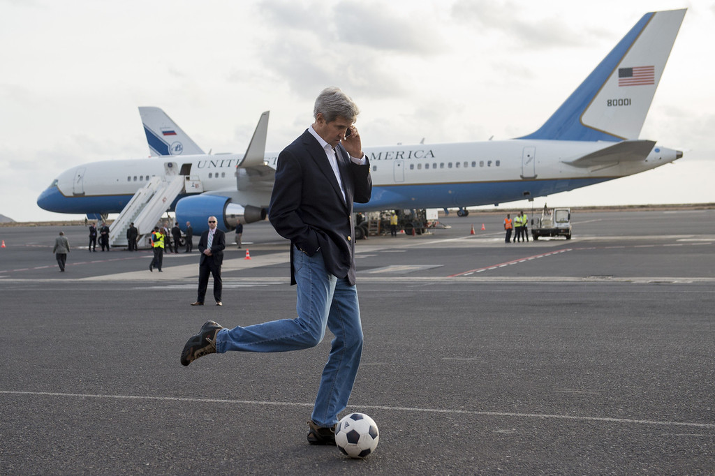 . U.S. Secretary of State John Kerry kicks around a soccer ball while talking on his cellphone during an airplane refueling stop at Sal Island, Cape Verde, enroute to Washington, DC, May 5, 2014. AFP PHOTO / POOL / Saul  LOEB/AFP/Getty Images