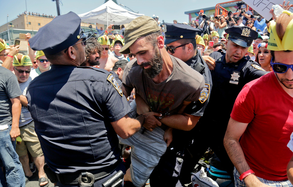. Police remove an animal rights activist as they try to protest at the Nathan\'s Annual Famous International Hot Dog Eating Contest won by Joey Chestnut, Tuesday July 4, 2017, in New York. (AP Photo/Bebeto Matthews)