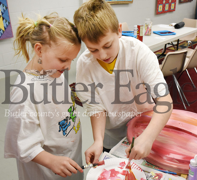 Harold Aughton/Butler Eagle: (left - right) Siblings Clara, 8, and Jack, 11, Peterson of Zelienople work together to paint the lid of a rain barrel as part of a class project for homeschoolers at the Zelienople Library, Tuesday, March 3, 2020.