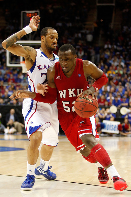 . KANSAS CITY, MO - MARCH 22: T.J. Price #52 of the Western Kentucky Hilltoppers drives against Travis Releford #24 of the Kansas Jayhawks in the second half during the second round of the 2013 NCAA Men\'s Basketball Tournament at the Sprint Center on March 22, 2013 in Kansas City, Missouri.  (Photo by Ed Zurga/Getty Images)