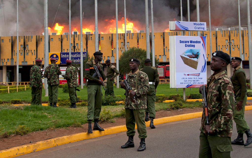 . Armed policemen cordon off the area as fire rages at the international arrivals unit of Jomo Kenyatta International Airport, Nairobi, Kenya, Wednesday, Aug. 7, 2013.  (AP Photo/Sayyid Azim)