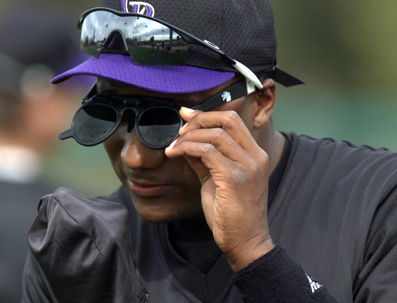 . Darryl Hamilton cleans off a pair of flip-up sunglasses for outfield training in Tucson Friday morning.