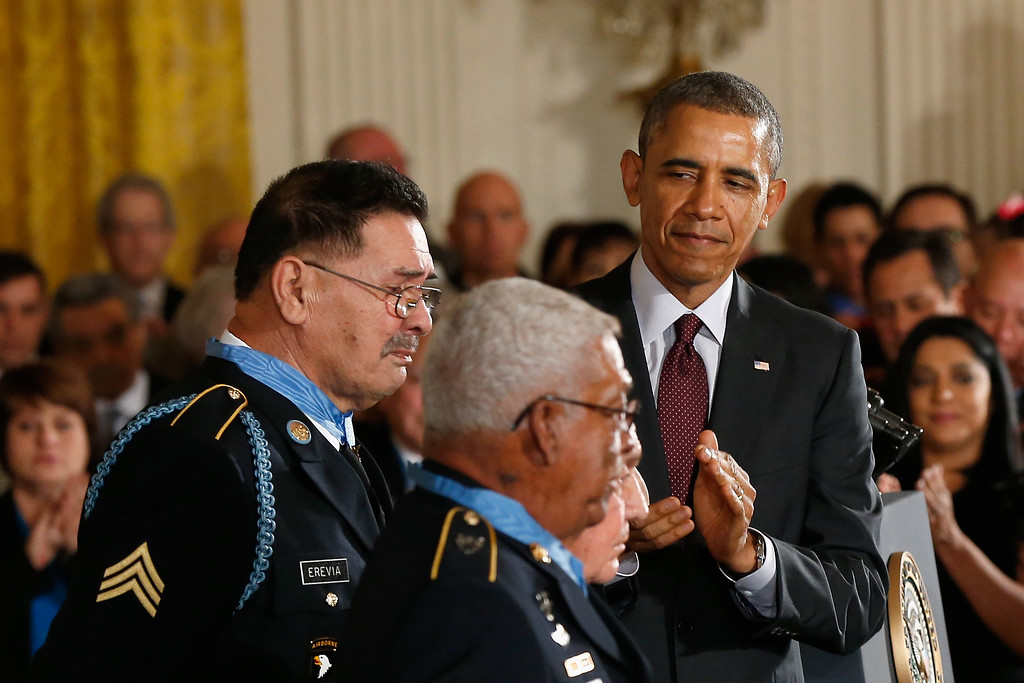 . U.S. Army Staff Sgt. (Ret.) Melvin Morris (2L), Sgt. First Class (Ret.) Jose Rodela (obscured) and U.S. Army Specialist Four (Ret.) Santiago J. Erevia (L) are applauded after receiving the Medal of Honor from U.S. President Barack Obama at the White House on March 18, 2014 in Washington, DC.   (Photo by Win McNamee/Getty Images)