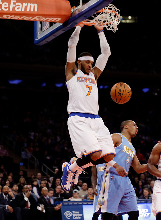 . New York Knicks\' Carmelo Anthony (7) dunks next to Denver Nuggets\' Randy Foye (4) during the first half of an NBA basketball game Friday, Feb. 7, 2014, in New York. (AP Photo/Frank Franklin II)