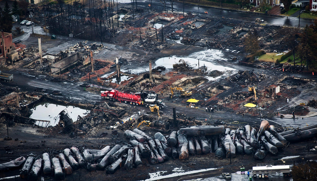 . FOR USE AS DESIRED, YEAR END PHOTOS - FILE - Workers comb through debris Tuesday, July 9, 2013, after a train derailed Saturday causing explosions of railway cars carrying crude oil in Lac-Megantic, Quebec. (AP Photo/The Canadian Press, Paul Chiasson, File)