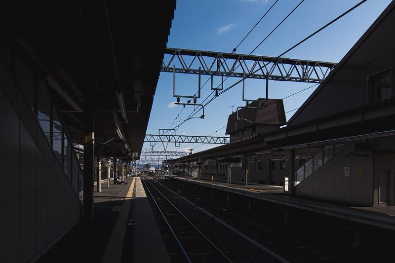Man Waiting at Japanese Train Station in Tokyo