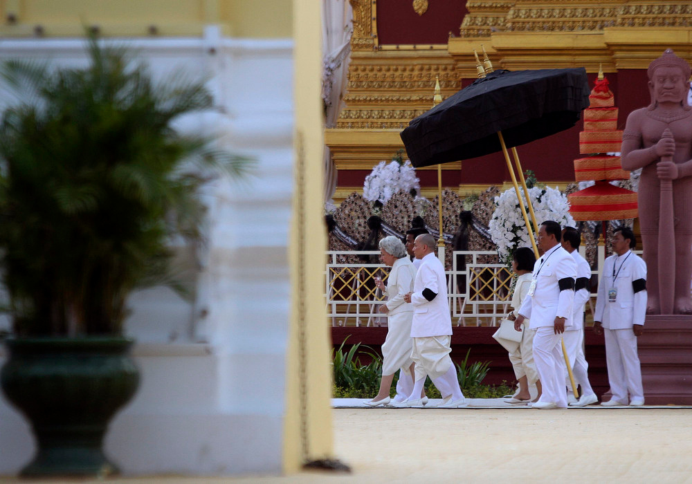 . Queen Mother Monineath Sihanouk (L) and King Norodom Sihamoni (2nd L) walk during the cremation ceremony of Cambodia\'s late King Norodom Sihanouk in Phnom Penh February 4, 2013. Tens of thousands of Cambodians gathered on Monday to pay their last respects to former King Norodom Sihanouk, a quixotic and much-loved figure who reigned during the country\'s struggle for independence but was powerless to prevent decades of war. REUTERS/Samrang Pring