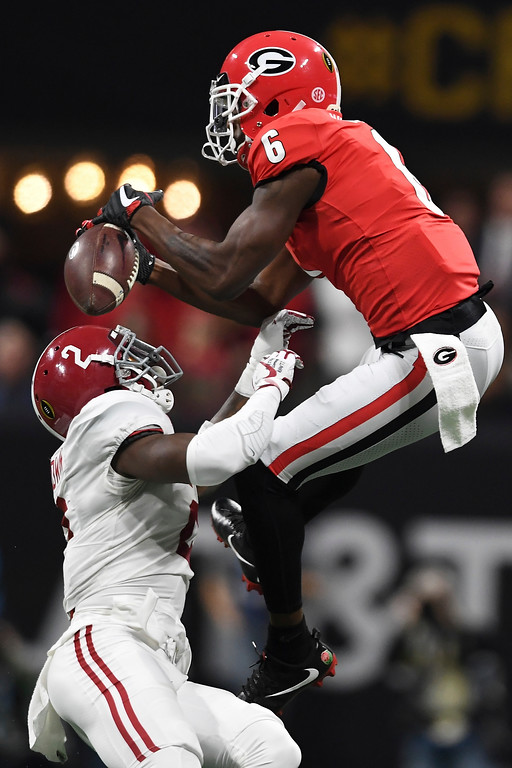 . Georgia wide receiver Javon Wims (6) bobbles a ball which is intercepted by Alabama defensive back Tony Brown (2) in the NCAA college football playoff championship game in Atlanta on Monday, Jan. 8, 2018. (AJ Reynolds/Athens Banner-Herald via AP)