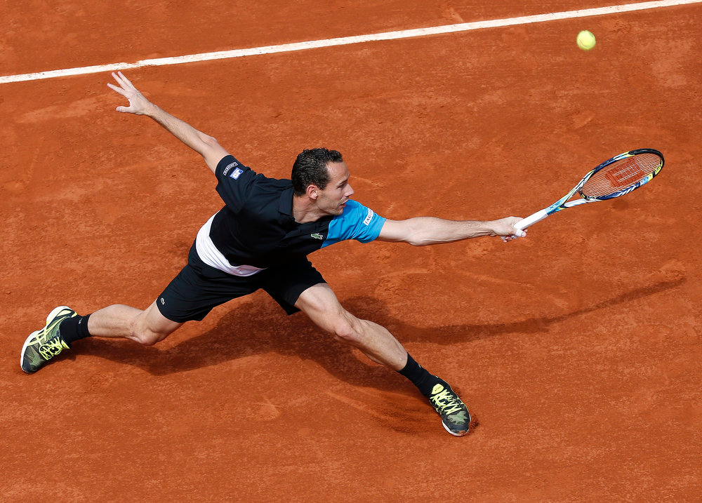 . France\'s Michael Llodra hits a backhand shot to Canada\'s Milos raonic during a French tennis Open match at the Roland Garros stadium in Paris on May 29, 2013. THOMAS COEX/AFP/Getty Images