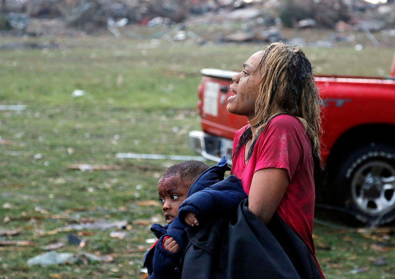 . A woman carries an injured child to a triage center near the Plaza Towers Elementary School in Moore, Okla., Monday, May 20, 2013. A tornado as much as a mile (1.6 kilometers) wide with winds up to 200 mph (320 kph) roared through the Oklahoma City suburbs Monday, flattening entire neighborhoods, setting buildings on fire and landing a direct blow on an elementary school. (AP Photo Sue Ogrocki)