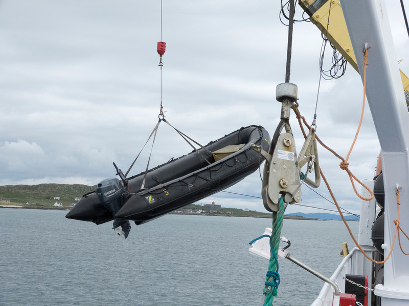 1 of the Zodiacs being craned off