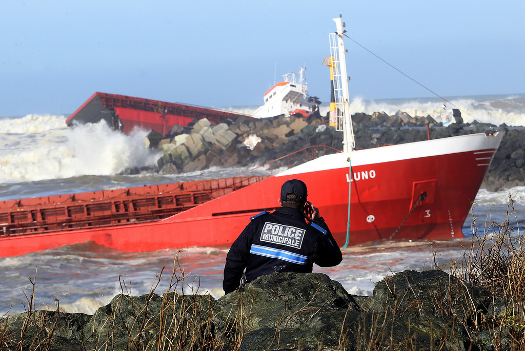 . A police officer watches a Spanish cargo ship that slammed into a jetty in choppy Atlantic Ocean waters and broke in two, off Anglet, southwestern France, Wednesday, Feb. 5, 2014.   (AP Photo/Bob Edme)
