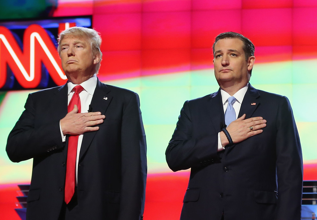 ". File - Republican presidential candidates Donald Trump and Sen. Ted Cruz (R-TX), listen to the national anthem before the start of the CNN, Salem Media Group, The Washington Times Republican Presidential Primary Debate on the campus of the University of Miami on March 10, 2016 in Coral Gables, Florida. Cruz announced Friday, Sept. 23, 2016, he will vote for Donald Trump, a dramatic about-face for the Texas senator who previously called the New York businessman a ""pathological liar\"" and \""utterly amoral.\""  (Photo by Joe Raedle/Getty Images)"