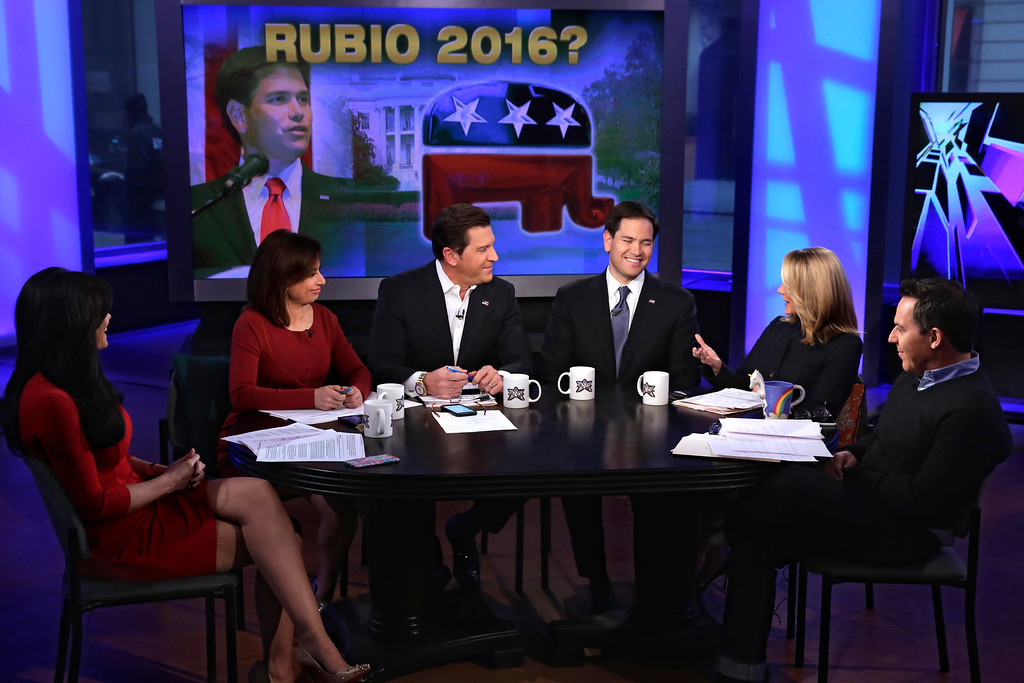 ". Fox News Channel co-hosts Kimberly Guilfoyle, Julie Roginsky, Eric Bolling, Dana Perino, and Greg Gutfeld, left to right, interview U.S. Sen. Marco Rubio, R-Fla., fourth left, on ""The Five\"" television program, on Fox News Channel, in New York, Monday, March 30, 2015. Closing in on an expected announcement that he will run for president, Sen. Marco Rubio said Monday that he is planning a political event in two weeks in Miami to announce his 2016 plans. The first-term Republican from Florida, appearing on Fox News, did not explicitly say he is running for the White House, instead telling would-be supporters to go to his website and reserve tickets for the rally. (AP Photo/Richard Drew)"