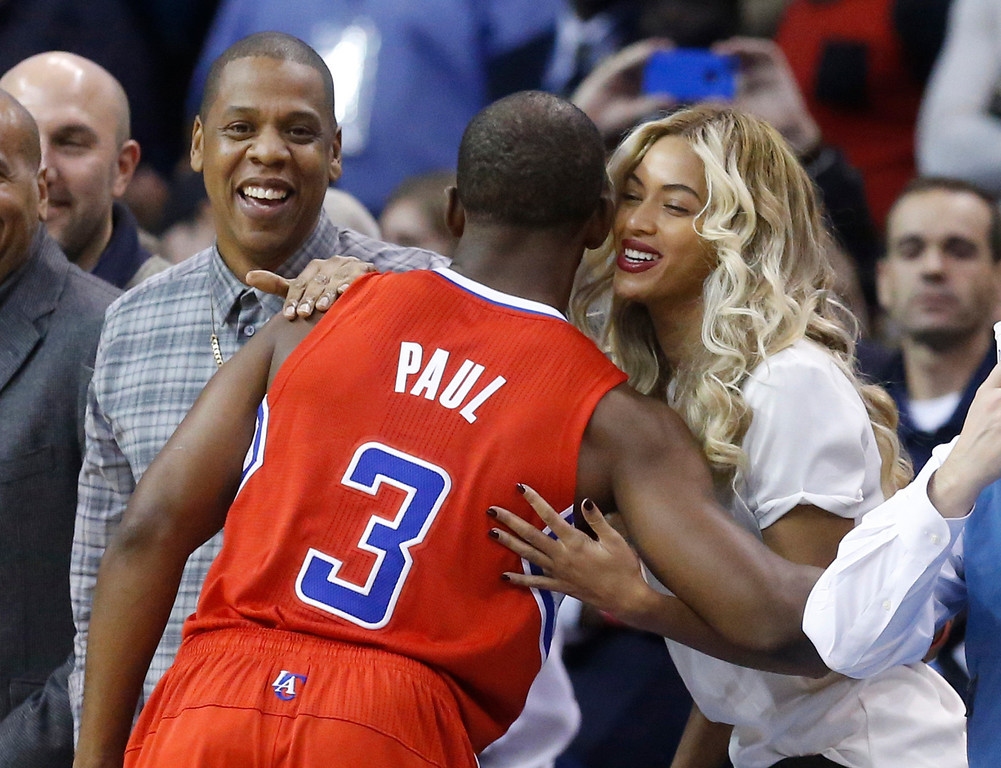 . Los Angeles Clippers guard Chris Paul (3) greets Jay-Z, left, and Beyonce, right, before the start of an NBA basketball game against the Oklahoma City Thunder in Oklahoma City, Thursday, Nov. 21, 2013. (AP Photo/Sue Ogrocki)