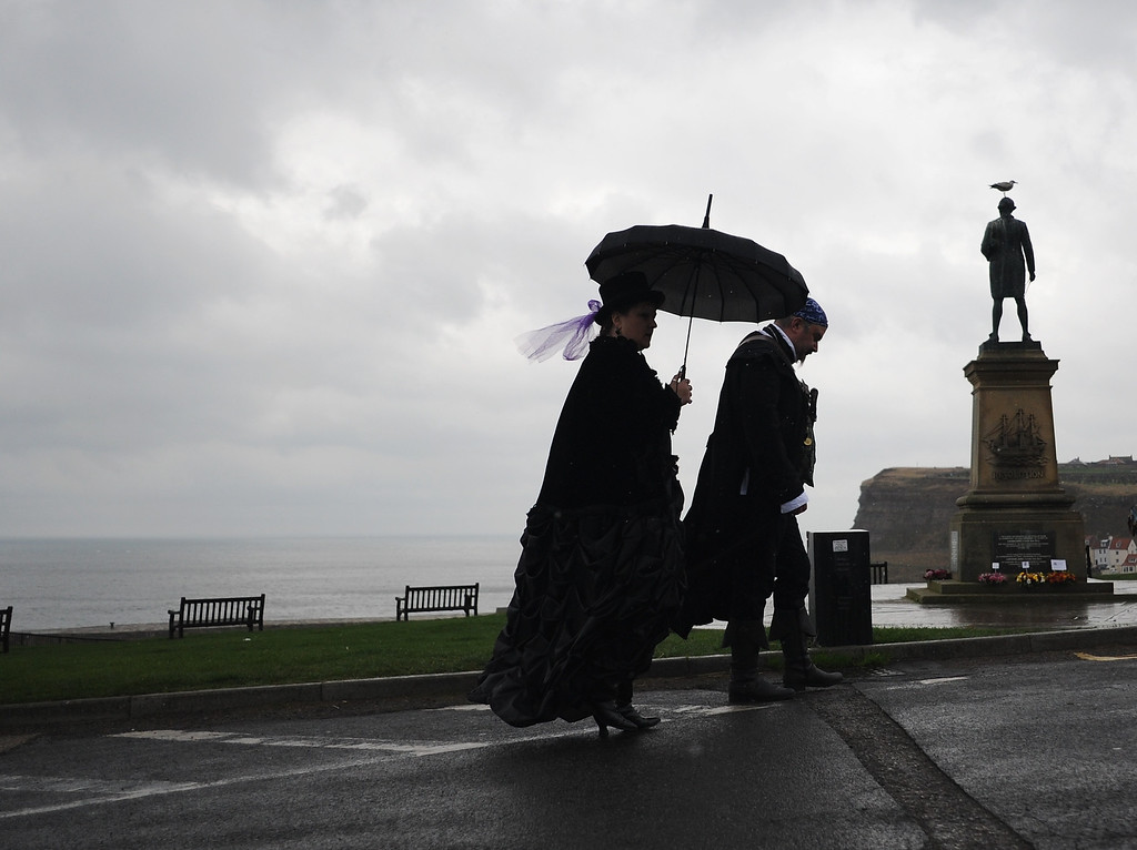 . WHITBY, ENGLAND - NOVEMBER 02: Two goths dressed in Victoriana style walk in the rain as they visit the Goth weekend on November 2, 2013 in Whitby, England. The Whitby Gothic Weekend that takes place in the Yorkshire seaside town twice yearly in Spring and Autumn started in 1994 and sees thousands of extravagantly dressed followers of Victoriana, Steampunk, Cybergoth and Romanticism visit to take part in celebrating Gothic culture.  (Photo by Ian Forsyth/Getty Images)