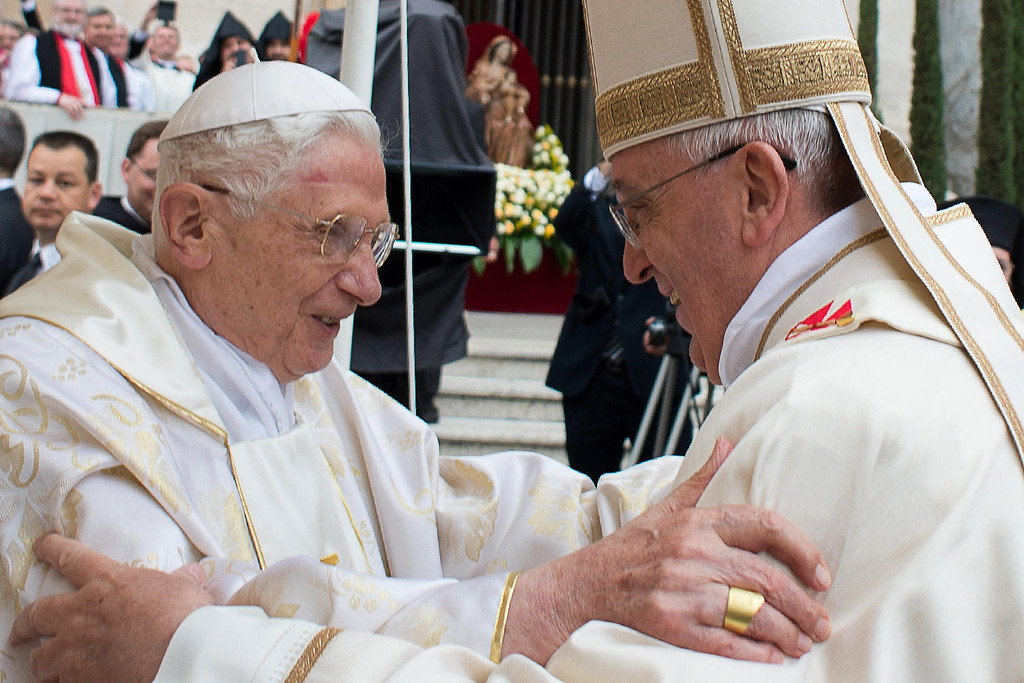 . ALTERNATIVE CROP - This handout picture released on April 27, 2014 by the Vatican press office shows Pope Francis (R) meeting with Pope emeritus Benedict XVI during the canonisation mass of Popes John XXIII and John Paul II on St Peter\'s square at the Vatican on April 27, 2014. Catholics from around the world gathered in Rome on Sunday for a mass presided by Pope Francis to confer sainthood on John Paul II and John XXIII -- two influential popes who helped shape 20th century history. AFP PHOTO / OSSERVATORE ROMANO