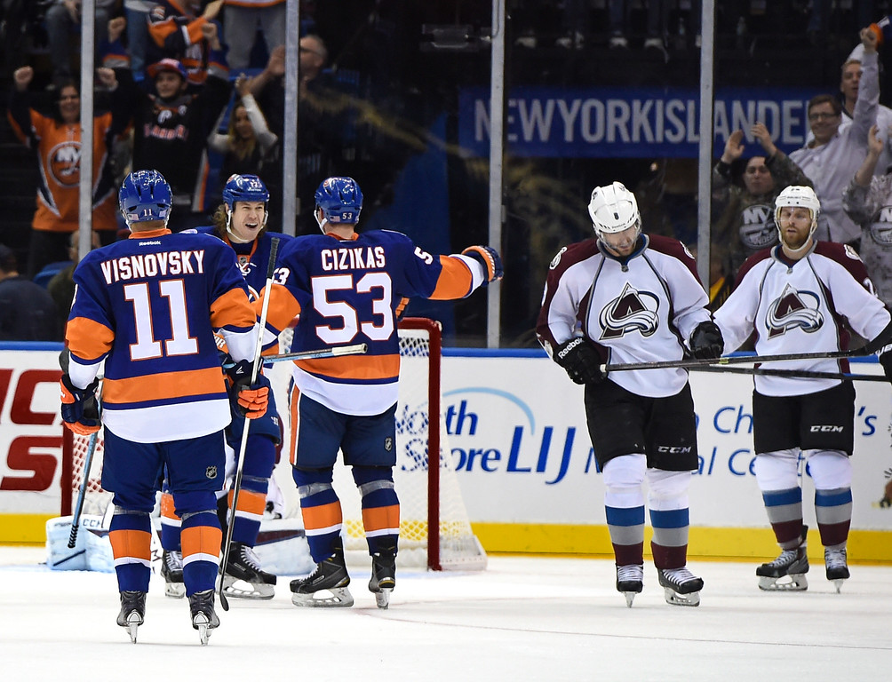 . New York Islanders defenseman Lubomir Visnovsky (11) and left wing Matt Martin (17) congratulate center Casey Cizikas (53) after Cizikas scored as Colorado Avalanche defenseman Jan Hejda (8) and center Marc-Andre Cliche (24), right, react in the third period of an NHL hockey game at Nassau Coliseum on Tuesday, Nov. 11, 2014, in Uniondale, N.Y. The Islanders won 6-0. (AP Photo/Kathy Kmonicek)