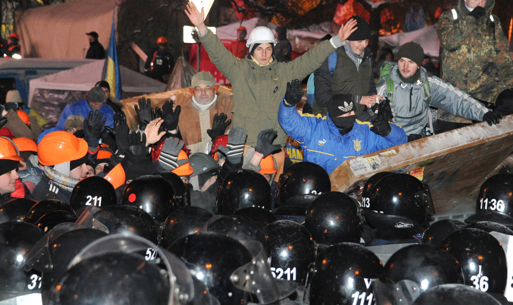 . Anti-Yanukovych protesters defend their barricades in front of anti-riot police on Independence Square in Kiev, early on December 11, 2013. Ukrainian security forces pulled out of the epicentre of mass protests in Kiev today after a nine hour standoff with thousands of demonstrators, in a major boost for the opposition to President Viktor Yanukovych. VIKTOR DRACHEV/AFP/Getty Images