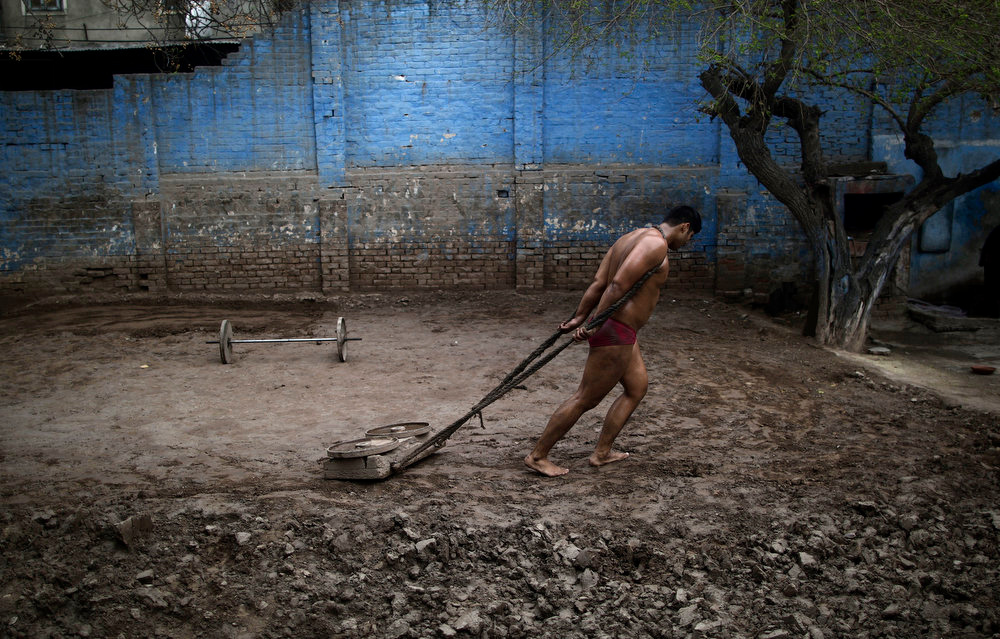 . A Pakistani Kushti wrestler prepares the soil in the ring, prior to a mach part of their daily training session, at a wrestling club in Lahore, Pakistan, Tuesday, Feb. 26, 2013. Kushti, an Indo-Pakistani form of wrestling, is several thousand years old and is a national sport in Pakistan. (AP Photo/Muhammed Muheisen)