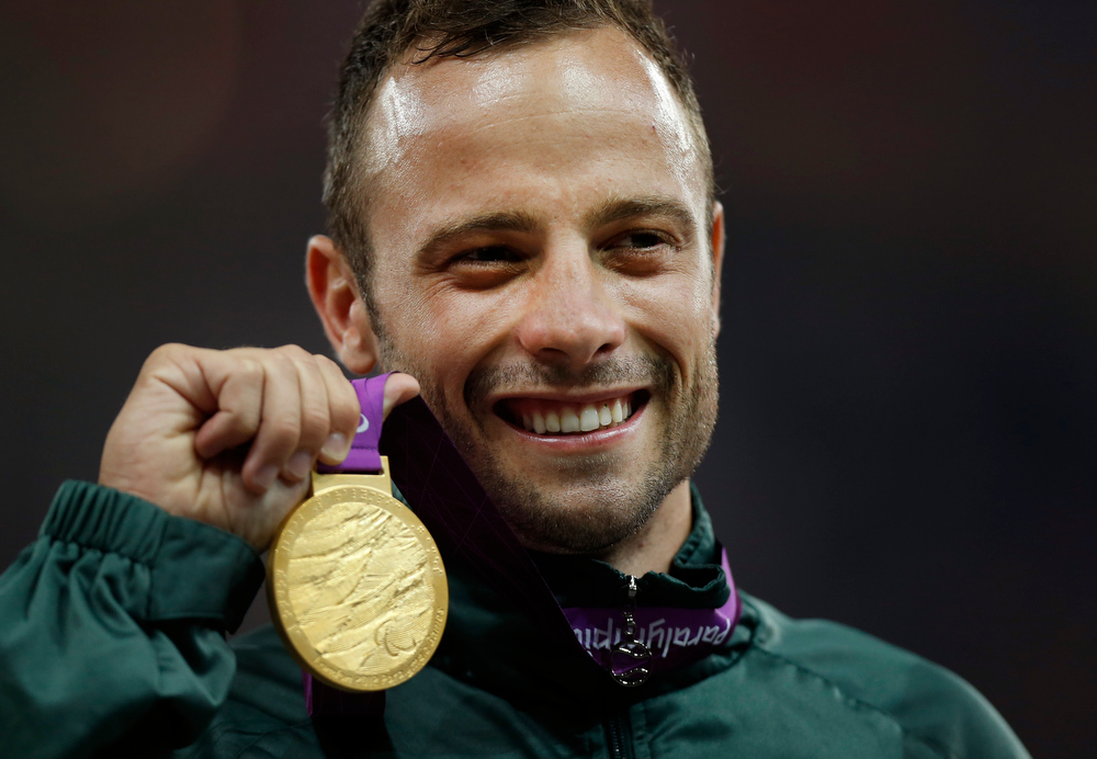 Description of . In this Saturday, Sept. 8, 2012, file photo, Gold medalist South Africa's Oscar Pistorius poses with his medal during the ceremony after winning the men's 400 meters T44 category final during the athletics competition at the 2012 Paralympics, in London. Olympic sprinter Oscar Pistorius has been arrested after a 30-year-old woman was shot dead at his home in South Africa. Police say Pistorius, a double-amputee known as