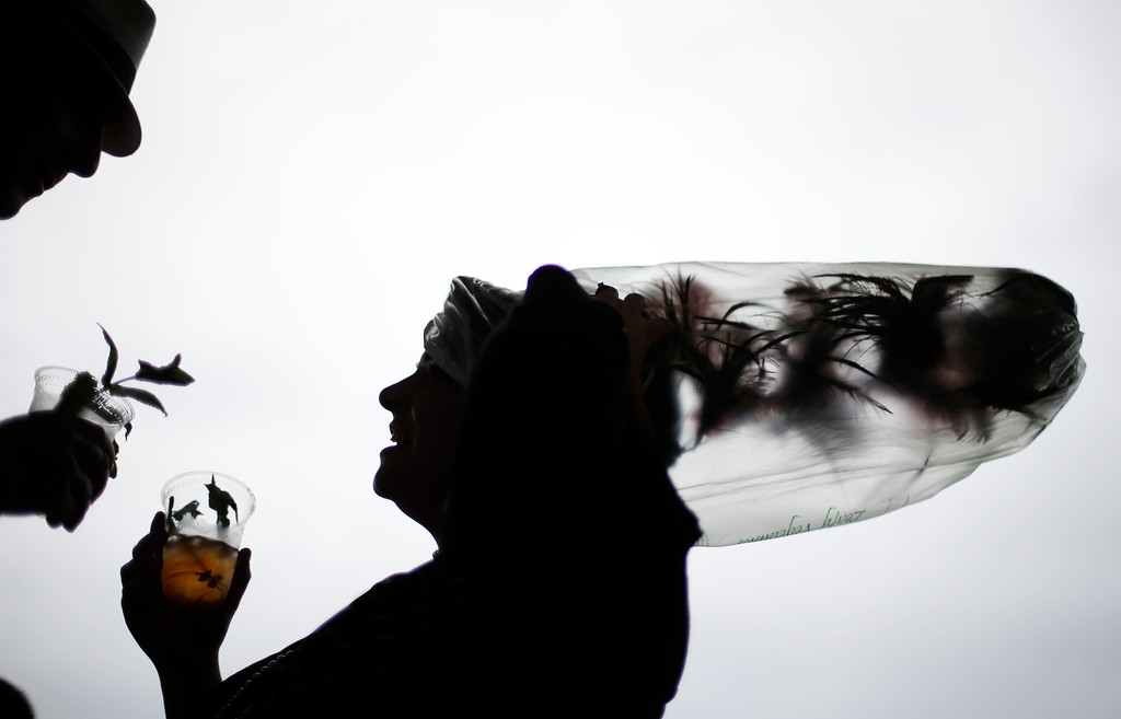 . Desirae Masterson, from Indianapolis, Ind., with her hat covered in a plastic bag to protect it from the rain, shares a mint julep with her husband Ray before the running of the 139th Kentucky Derby at Churchill Downs Saturday, May 4, 2013, in Louisville, Ky. (AP Photo/David Goldman)