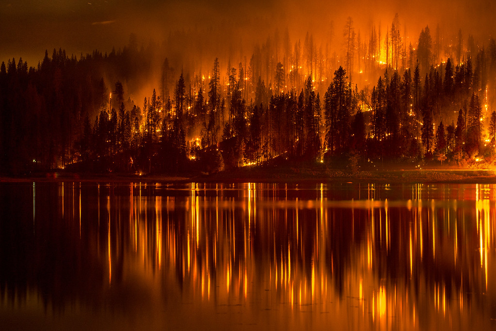 . This Sunday, Sept. 14, 2014 photo shows fire as it approaches the shore of Bass Lake, Calif. Crews are attempting to get better access to two raging wildfires in California on Monday that have forced hundreds to evacuate their homes. (AP Photo/YosemiteLandscapes.com, Darvin Atkeson )