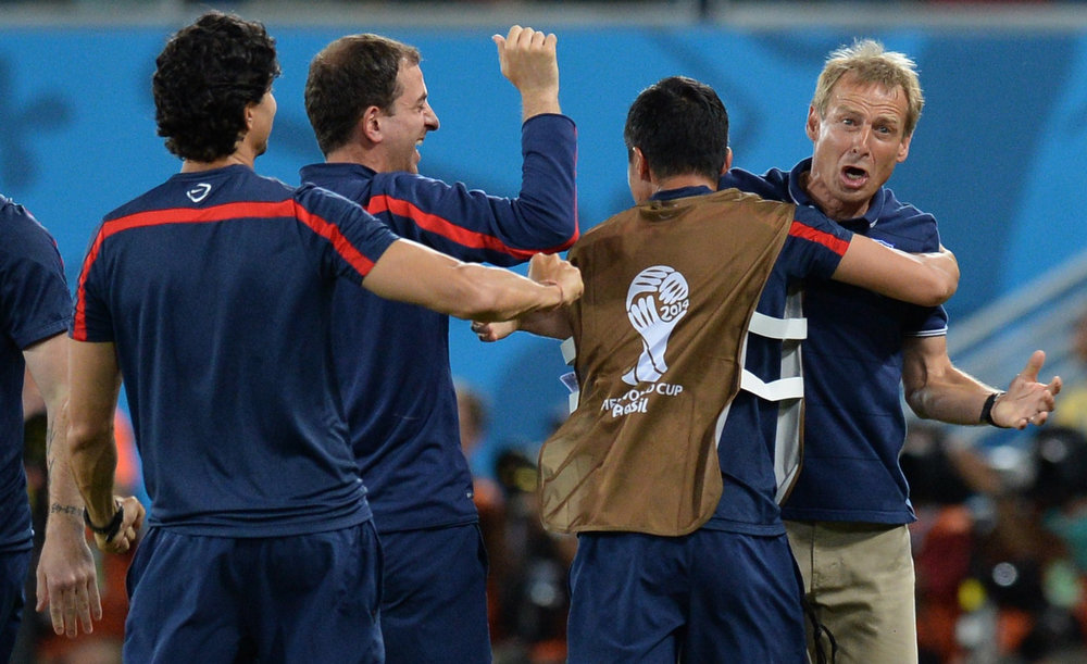. US German coach Juergen Klinsmann  (R) celebrates with teammates during a Group G football match between Ghana and US at the Dunas Arena in Natal during the 2014 FIFA World Cup on June 16, 2014.  AFP PHOTO / CARL DE SOUZACARL DE SOUZA/AFP/Getty Images