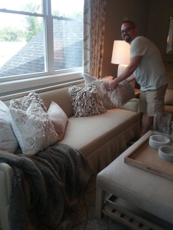 . Designer Greg Mononen of Gregory Todd Interiors in Mentor arranges pillows on a couch in the master suite of the 2018 Dream House. (Jean Bonchak)