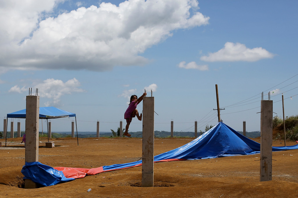 . A girl climbs up a post to get a better view of games as part of their Eid al-Fitr celebrations to mark the end of the Muslim holy fasting month of Ramadan in Marawi city, southern Philippines on Friday, June 15, 2018. Thousands of displaced residents celebrated Eid al-Fitr inside emergency shelters and the threat of Islamic extremists and unexploded bombs lingers in the rubble after a disastrous five-month siege by Islamic State group-aligned fighters that began more than a year ago. (AP Photo/Aaron Favila)