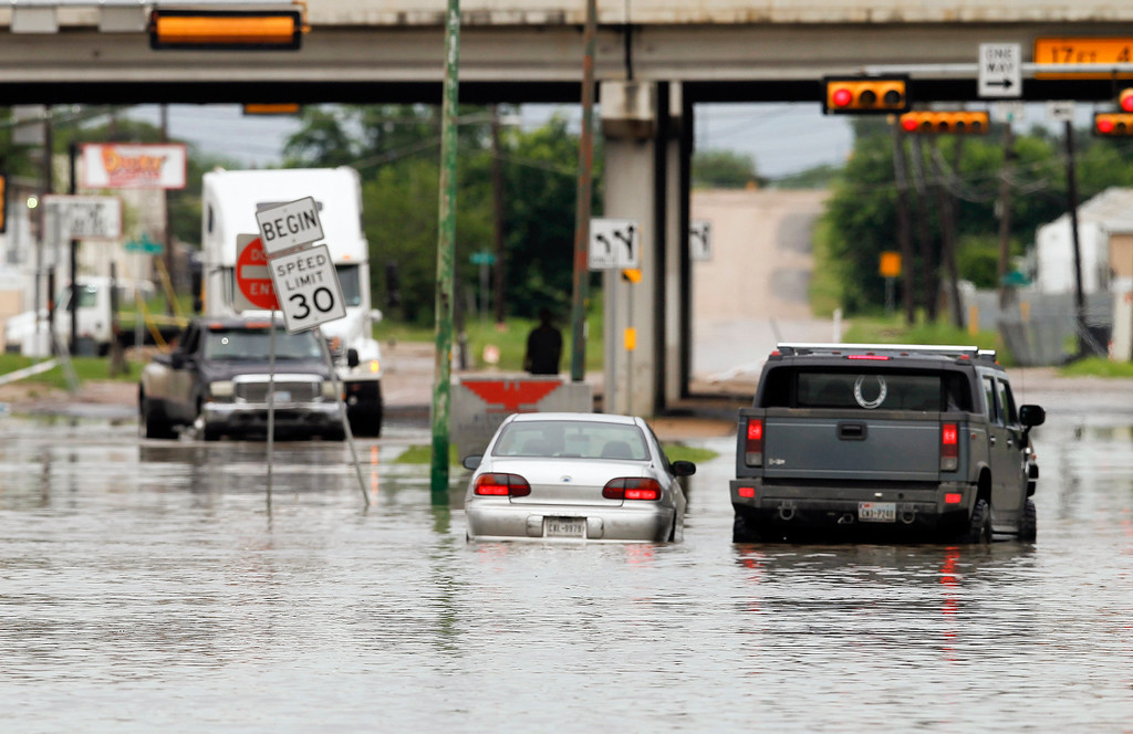 . A motorist stops to help another driver stranded in high water in Dallas on Saturday, May 30, 2015.  The National Weather Service has issued a flood watch for portions of Central and South Texas, which could see as much as five inches of rain Saturday if a storm system stalls over the area. (AP Photo/Rex C. Curry)