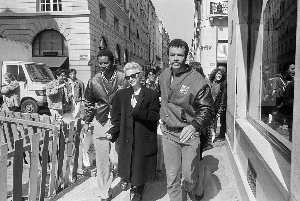 . Singer Madonna is surrounded by bodyguards and followed by fans as she walks on the Faubourg Saint Honore Street in Paris, Aug. 28, 1987. She gave two concerts in France, in Paris and Nice, French Riviera, after meeting French Premier Jacques Chirac to hand him a 500,000-franc ($83,000) check to help in AIDS research (AP Photo/Adeline Bommart)
