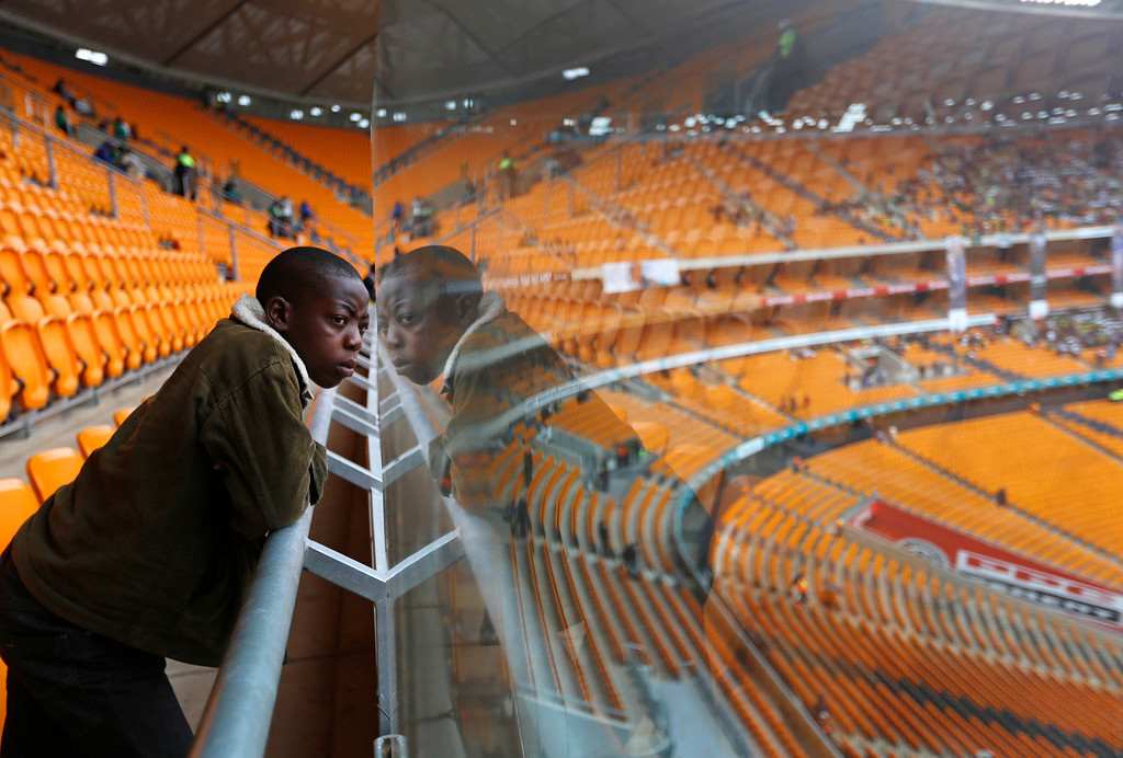 . 14-year-old Thomas is reflected in the glass of a security barrier as he look across the arena ahead of the memorial service for former South African president Nelson Mandela at the FNB Stadium in Soweto, near Johannesburg, South Africa, Tuesday Dec. 10, 2013. (AP Photo/Markus Schreiber)